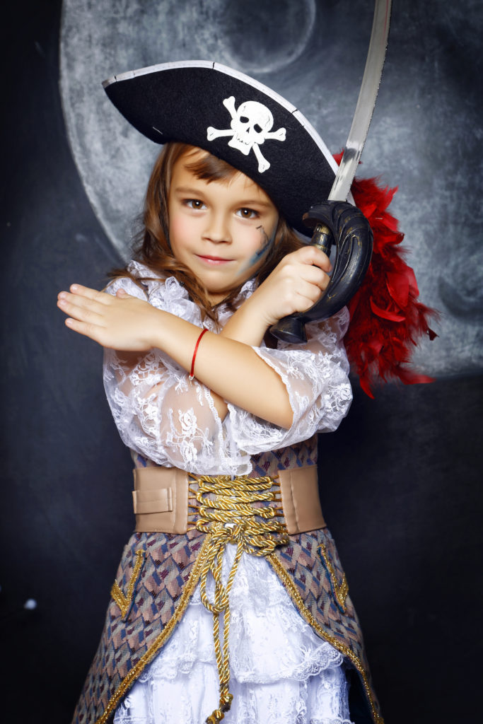 Little girl dressed in pirate costume on a black background with a moon image in a studio with Halloween decorations